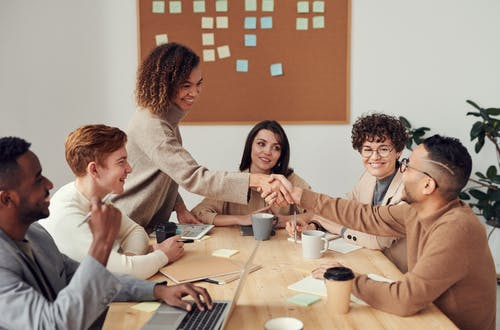 Diverse team sitting at a table working on a project, with two members shaking hands.