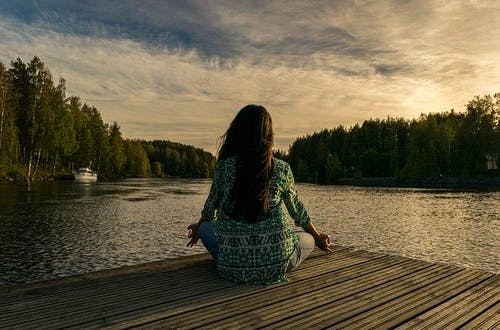Woman sitting cross legged practicing mindfulness meditation in front of a lake.