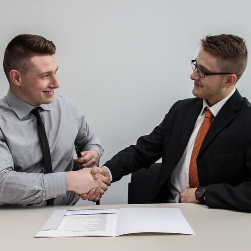Two businessmen shaking hands after a job interview.