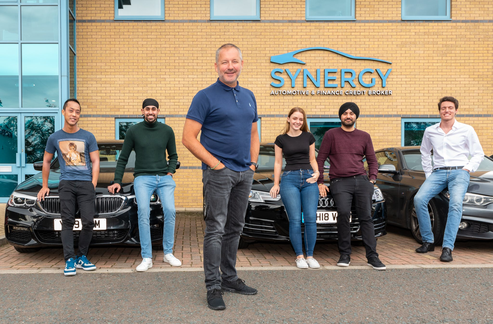 Six members of the Synergy Car Leasing team standing outside their offices.