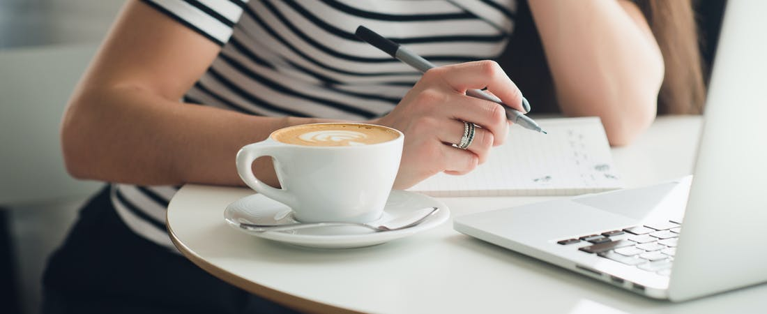 Woman writing on a notepad with coffee and laptop