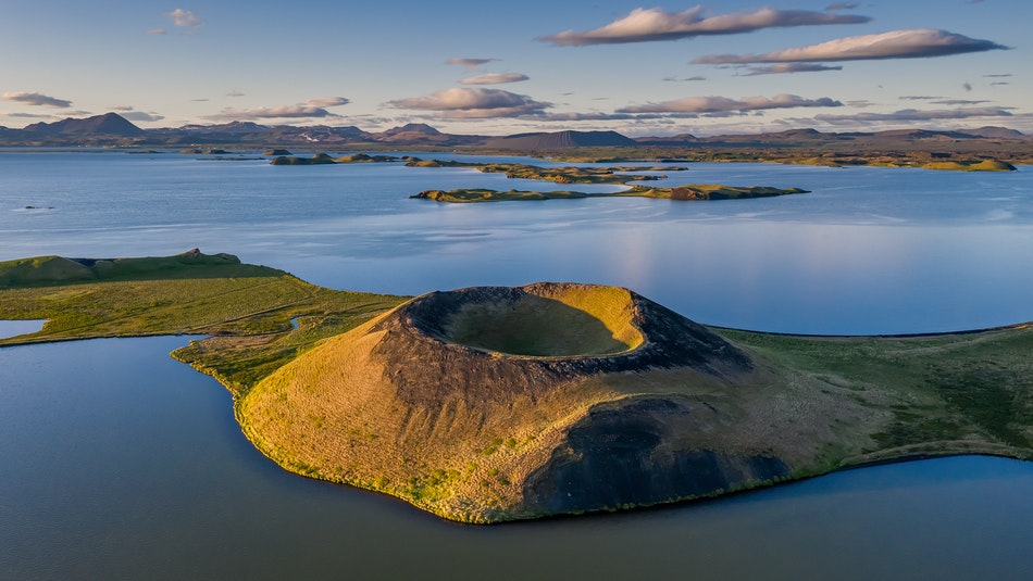 A volcanic crater in North Iceland with a lake and mountains in the background. Peaceful nature in Iceland.
