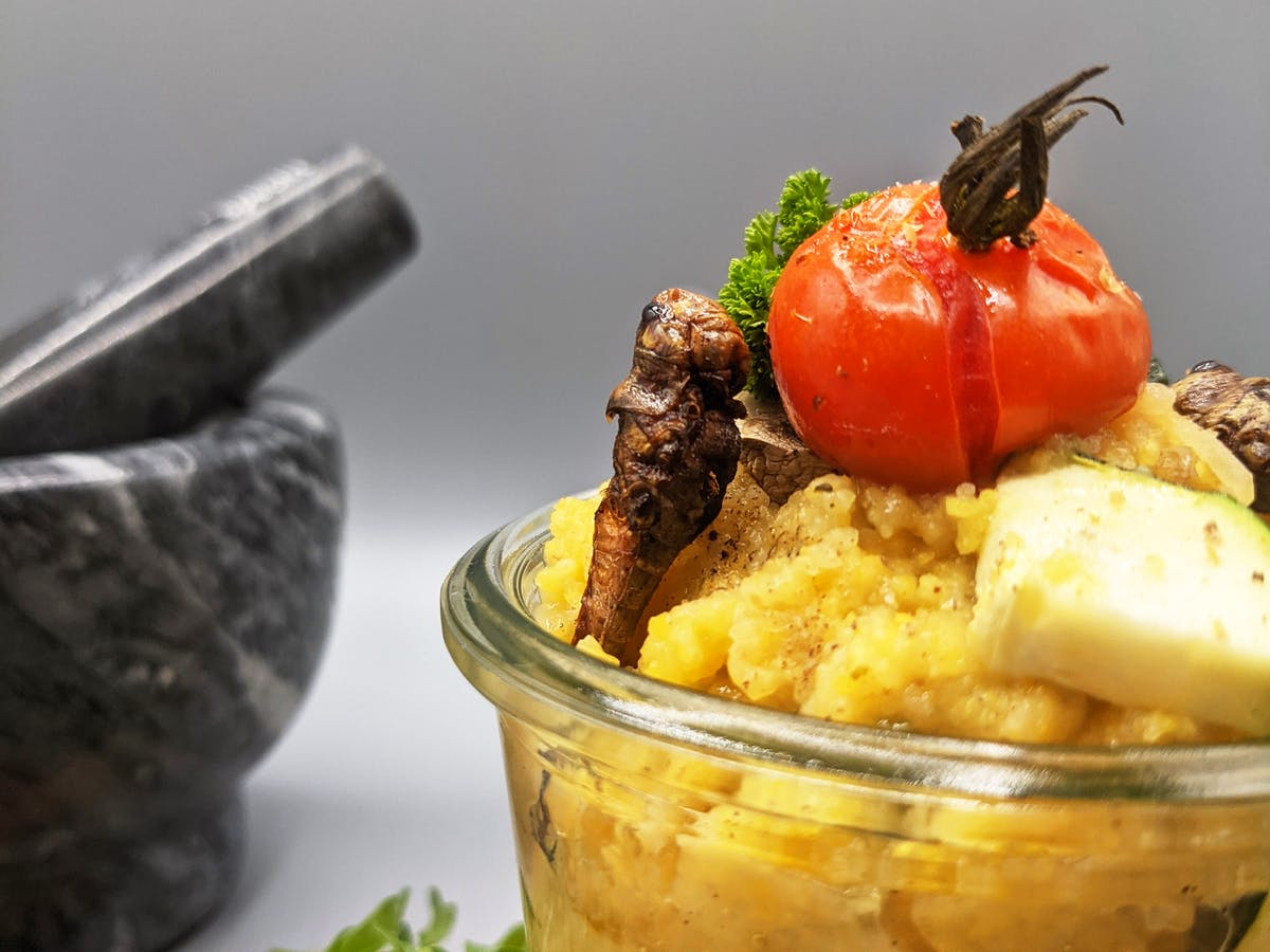 Grasshopper polenta in a jar topped with a grilled cherry tomato