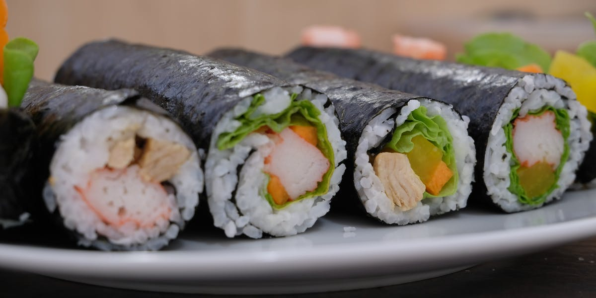 Four sushi rolls displayed on a plate