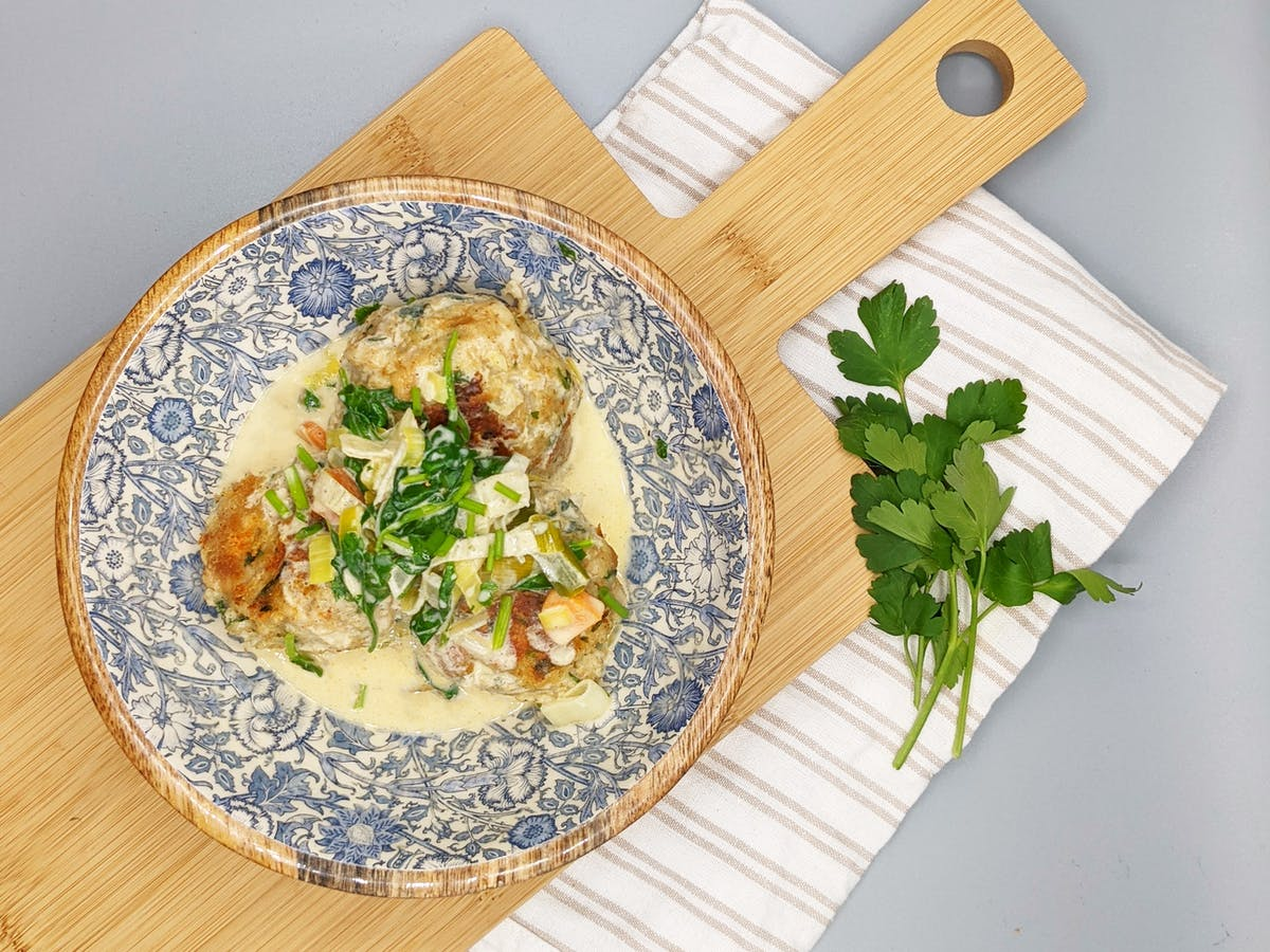 A bowl filled with Cricket dumplings in creamy sauce