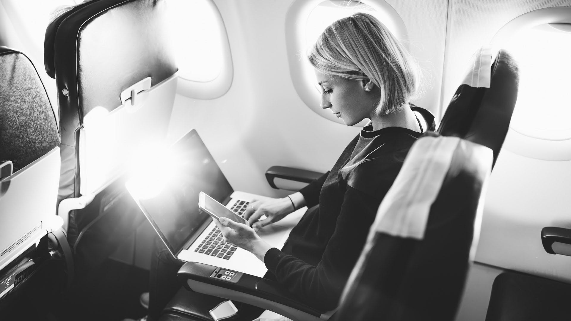 Employee working on a computer on board an aircraft