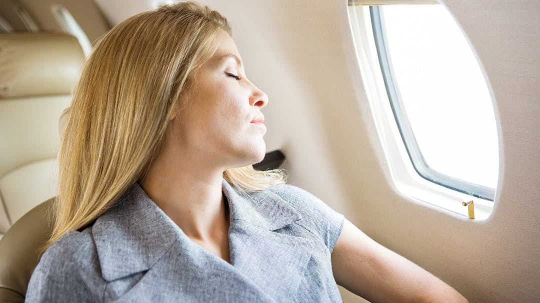 A woman enjoys a relaxing flight on a chartered plane