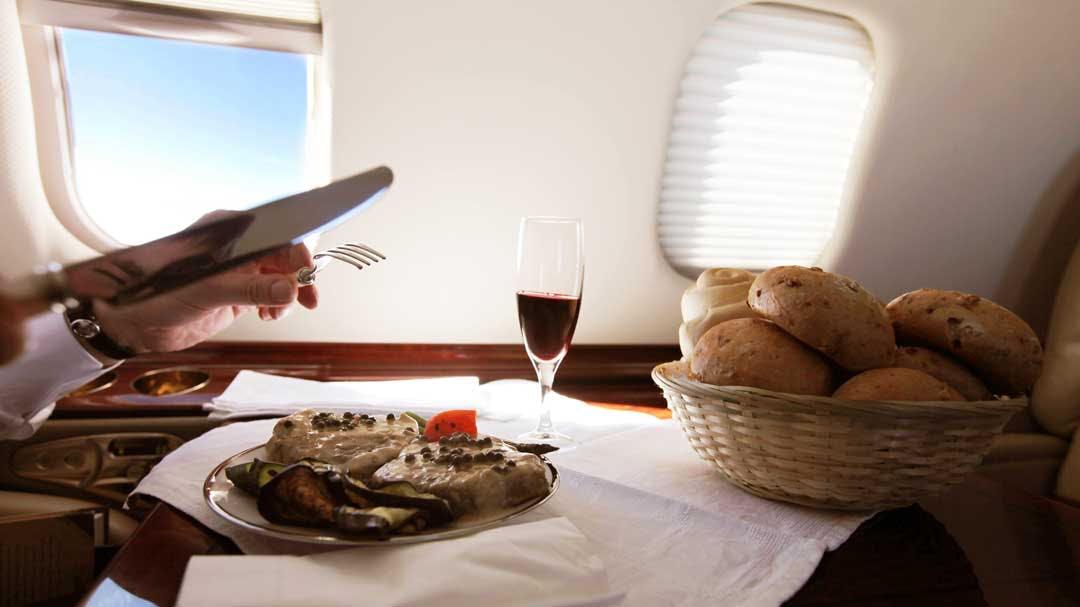 A private charter passenger enjoys a gourmet breakfast onboard their flight