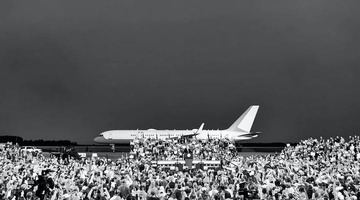 People attending a political meeting in front of a plane