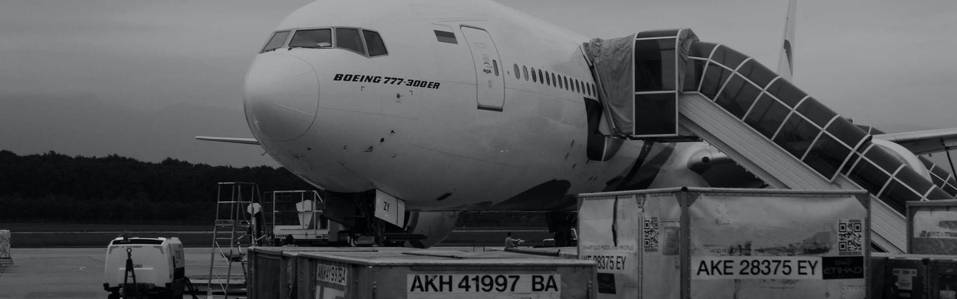 Two cargo containers in front of an aircraft boeing 777 300 ER that is waiting in the airport tarmac.