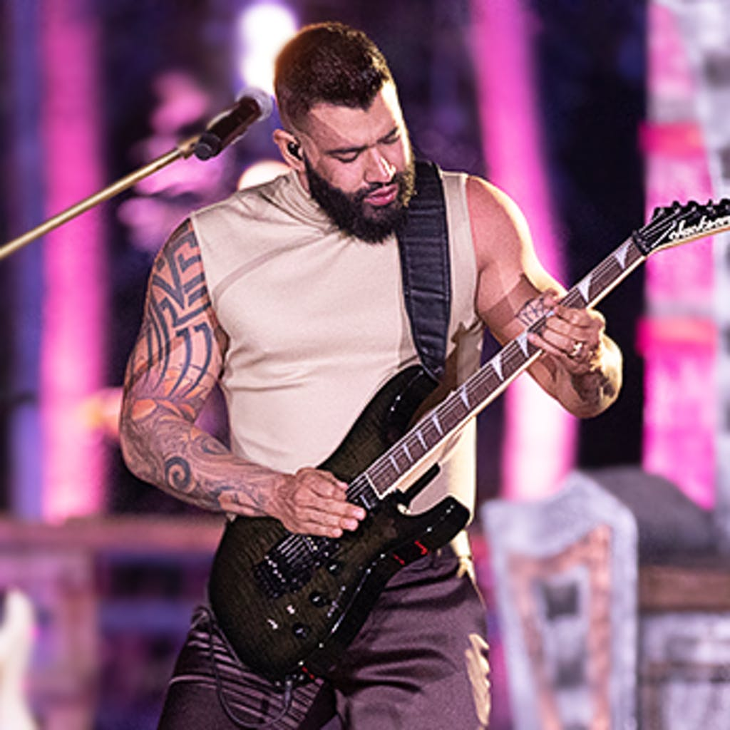 Cantor Gusttavo Lima tocando guitarra de cor preta.