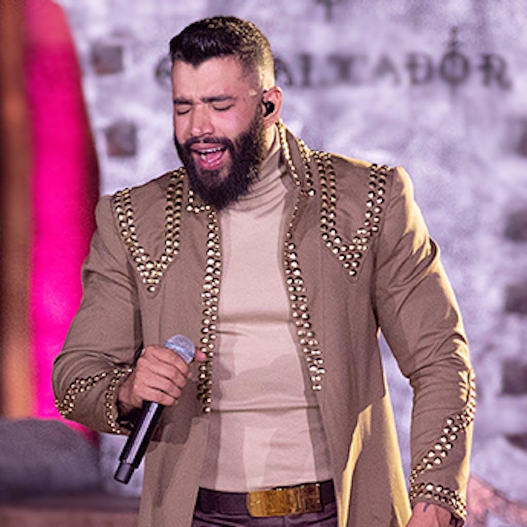 Gusttavo Lima usa um figurino de tons claros em um de seus shows.