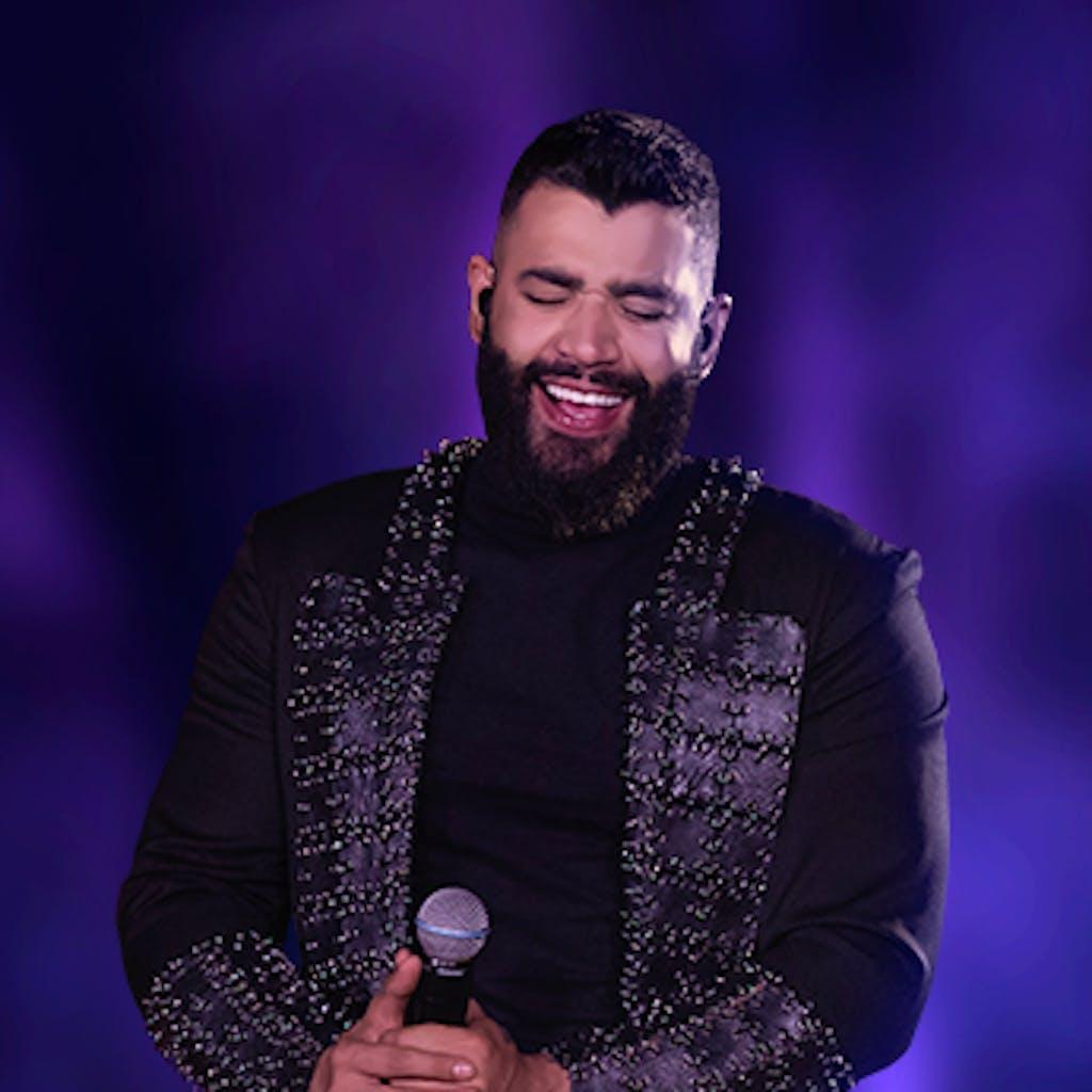 Gusttavo Lima usa uma roupa preta tipo medieval em um fundo esfumaçado de cor roxa.