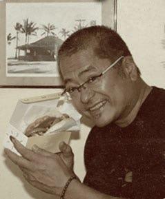 Photo of Hank Adaniya holding a haute dog