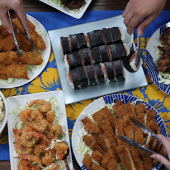 Buffet line with fried shrimp, garlic shrimp, chicken katsu, and musubi.