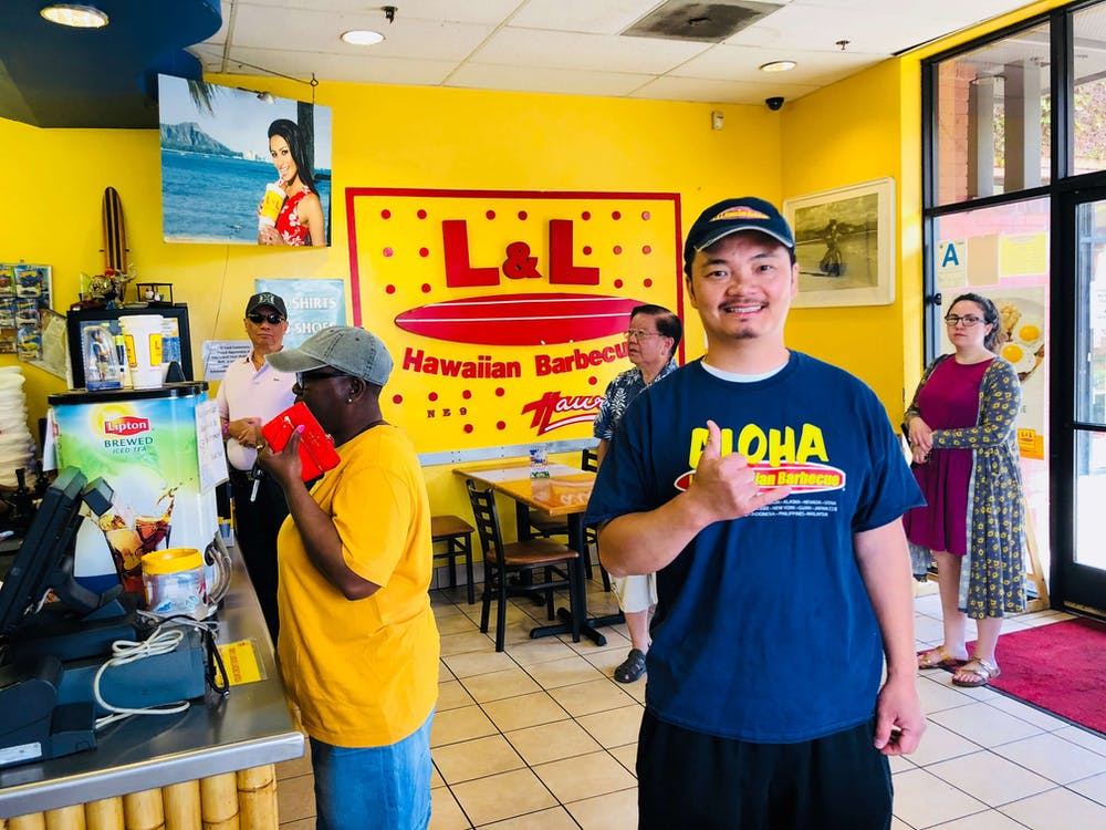 Happy franchisee in his L & L location with customers in background.