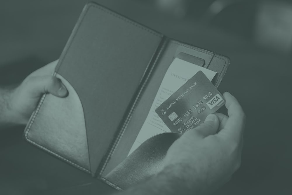 hands holding a restaurant tab and visa business credit card