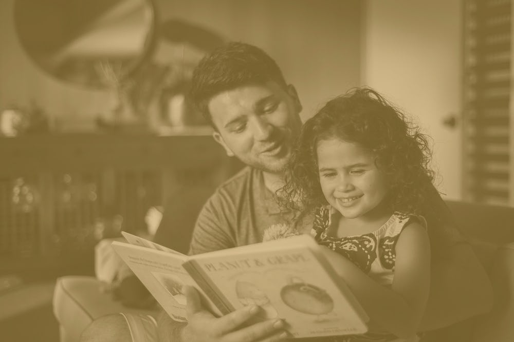 father reading daughter a children's book