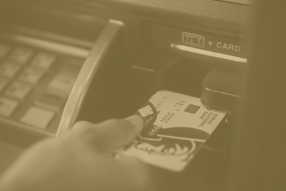 close up shot of hand inserting debit card into ATM