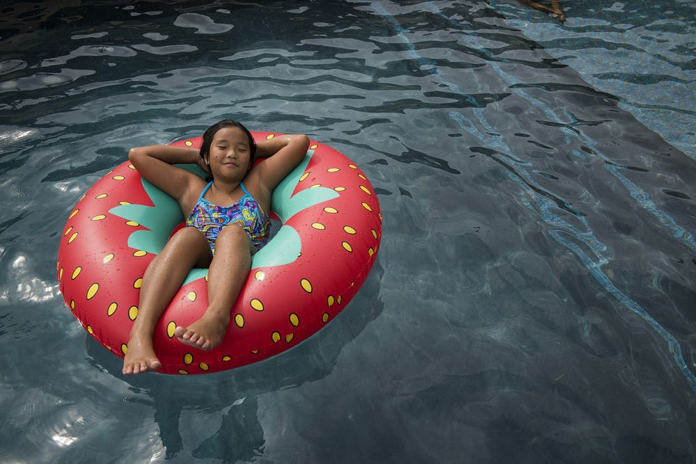 girl lounging on inflatable floatation device in pool