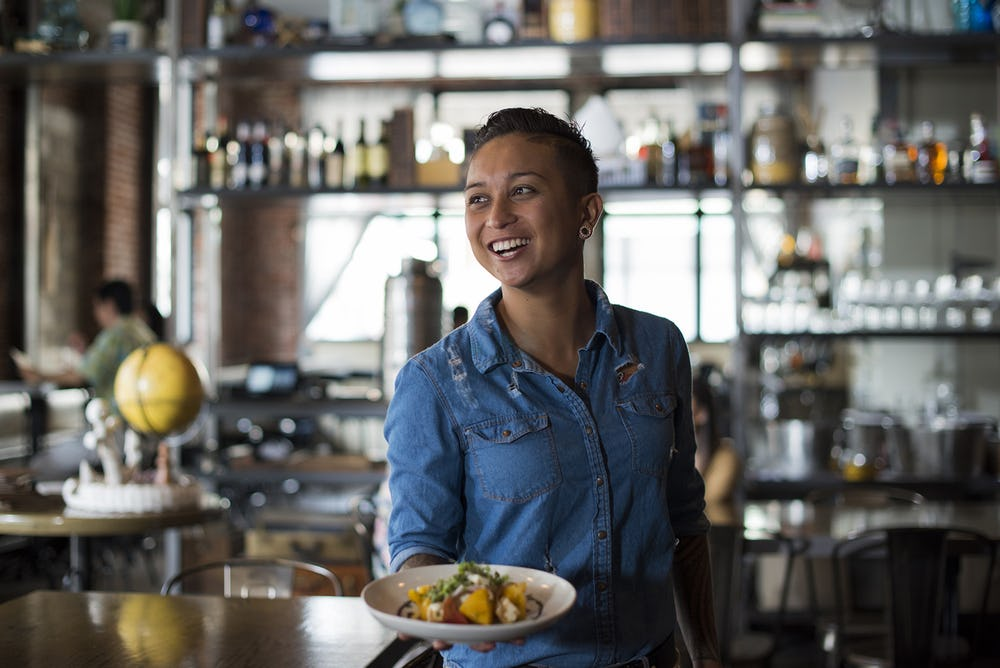 restaurant employee holding food and smiling