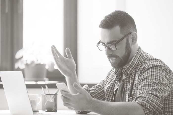 man looking at his cell phone at a desk