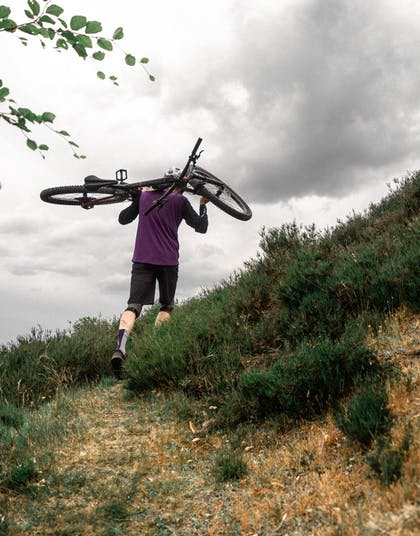 Morten der bærer sin cykel over ryggen