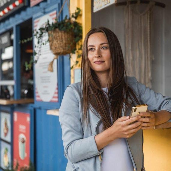 Emma foran en butik med sin mobiltelefon