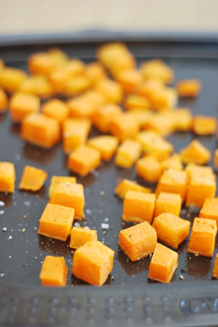 Cubed butternut squash, flaked with coarse grains of salt, on a baking tray