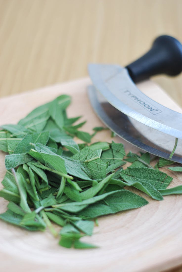 Whole leaves of sage, on a chopping board