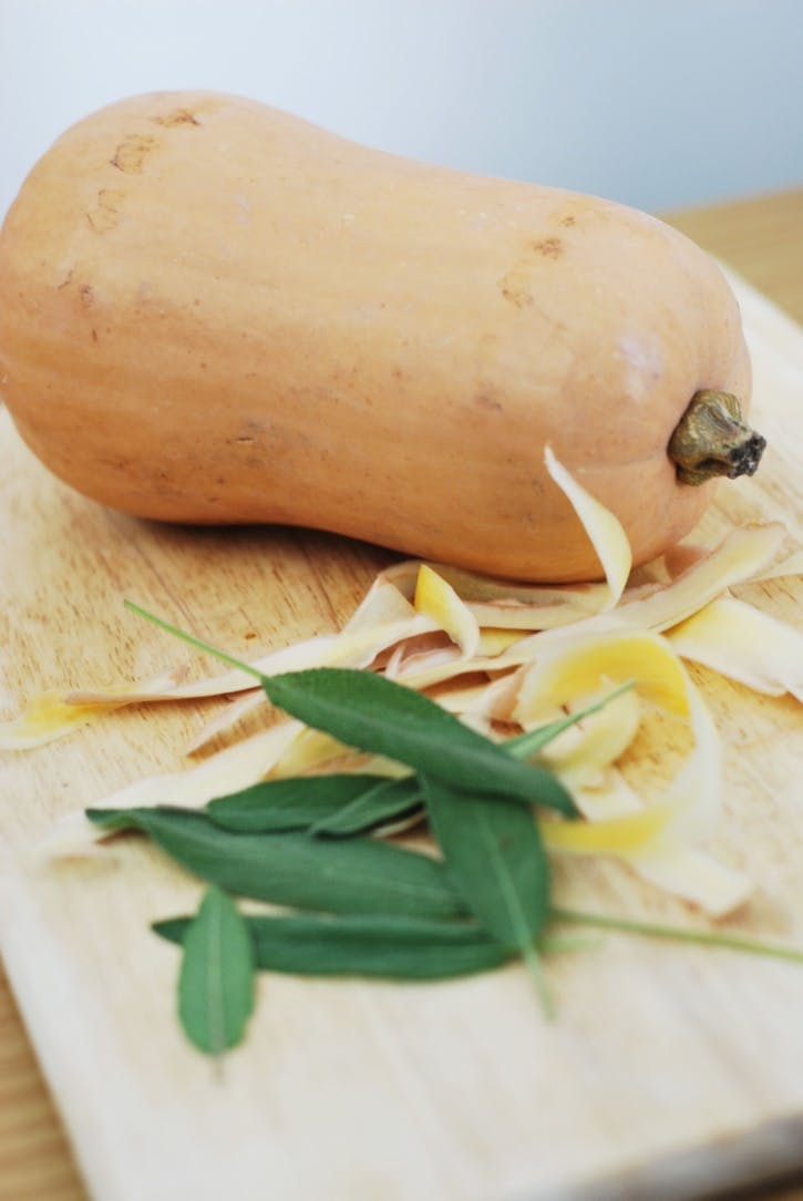 Butternut squash, sage leaves, and butternut squash peel, sitting on a chopping board