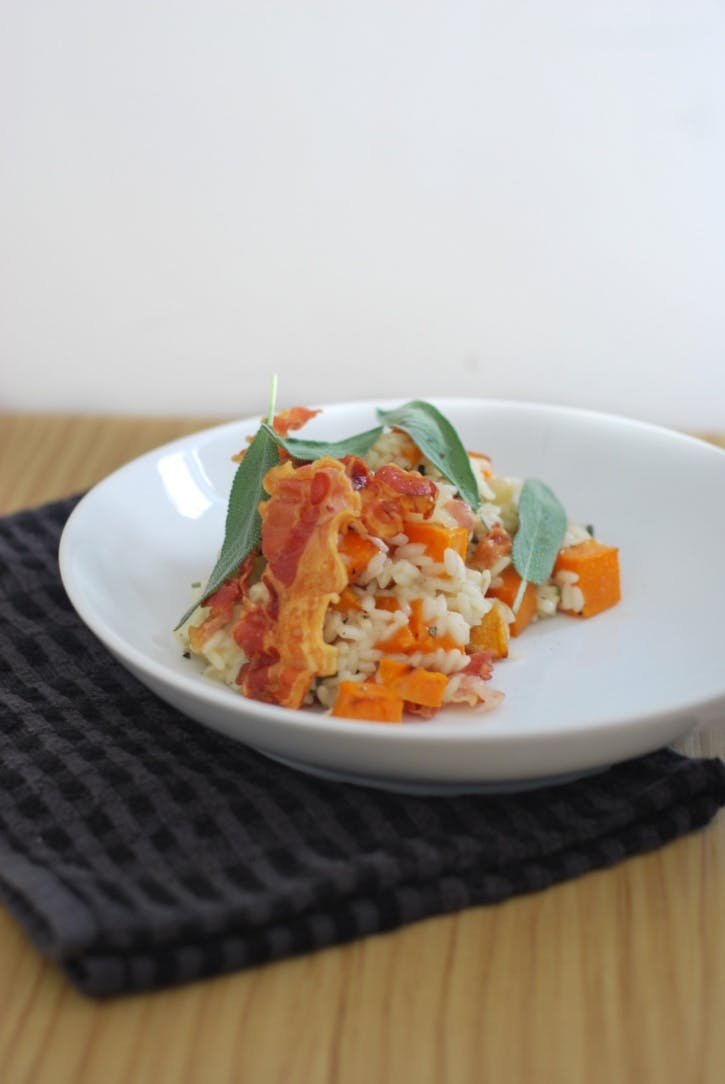 Butternut squash risotto, topped with crispy pancetta and sage, plated up in a shallow white bowl