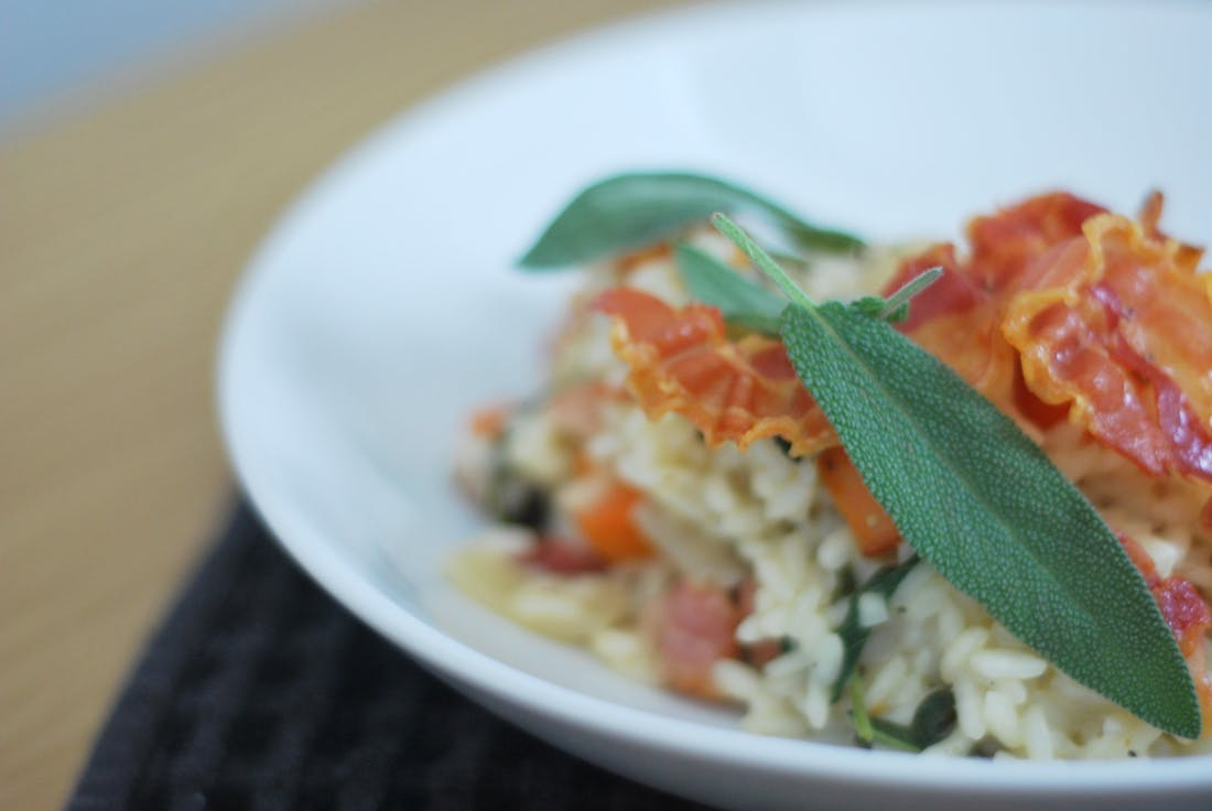 Close-up of the final dish of the risotto topped with crispy pancetta and whole sages leaves