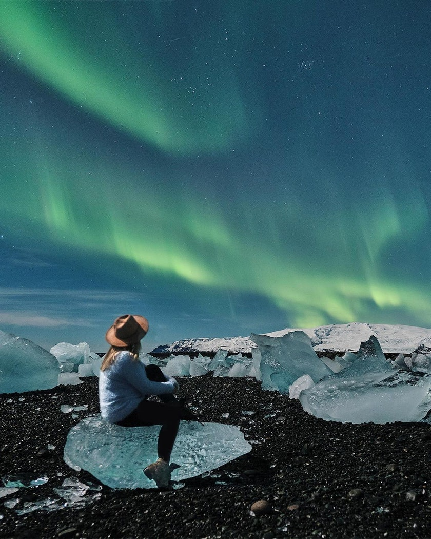 A lady watching the Northern Lights by the glacier lagoon. Photo by @_mishamartin