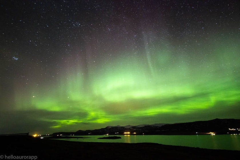 Intense aurora show over the fjord in Iceland