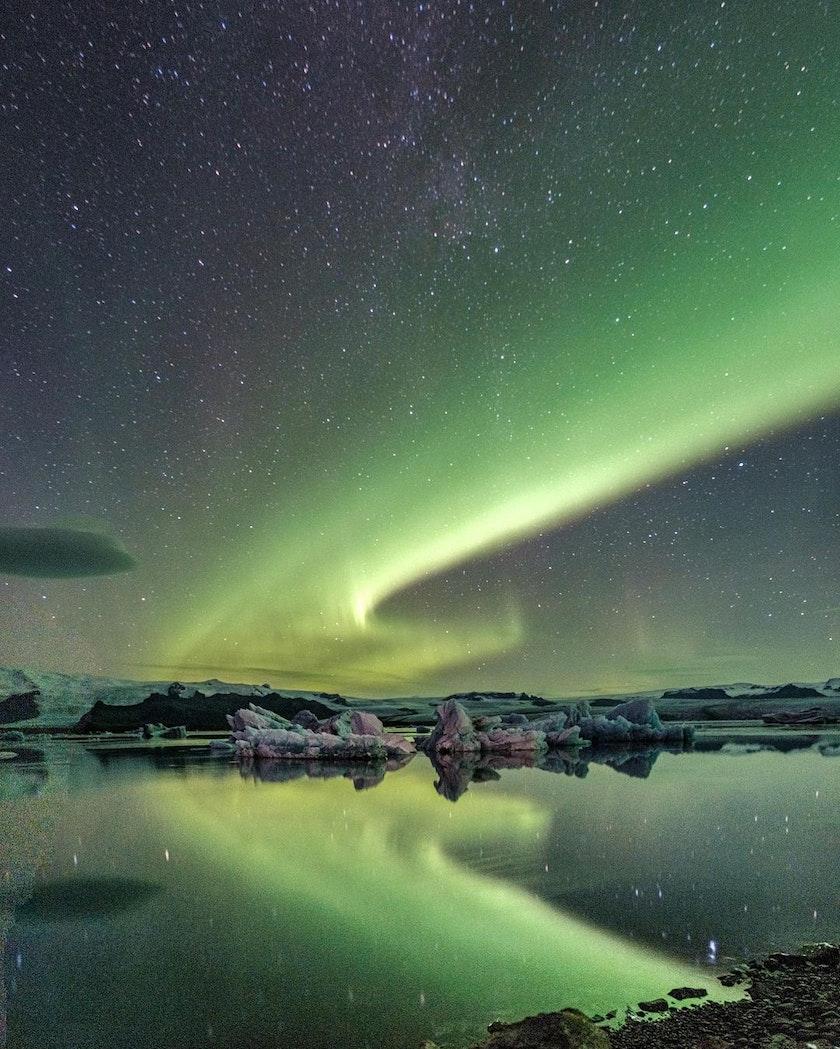 Northern Lights reflecting on the glacier lagoon nearby Höfn. Photo by @_mishamartin