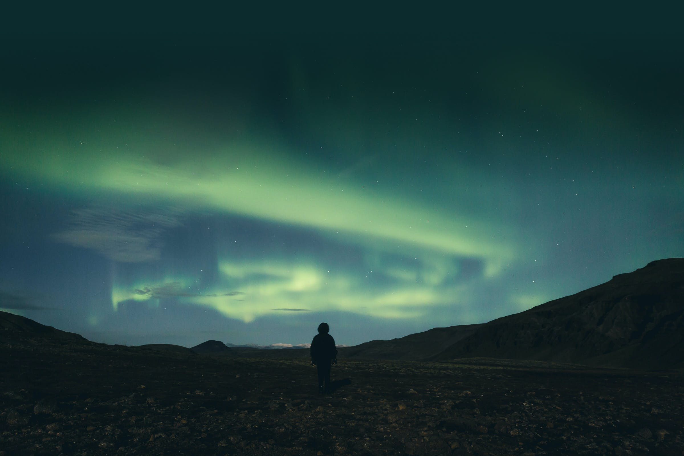 A person watching the Northern Lights over a mountain