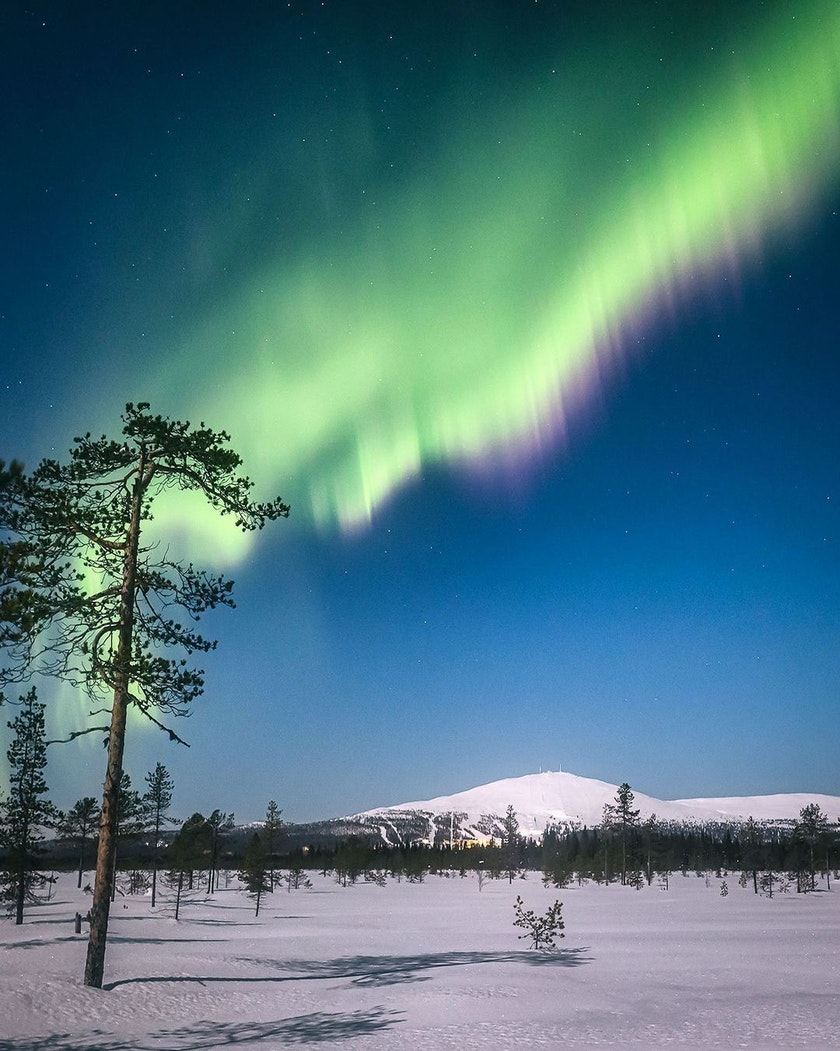 Bright aurora over the icy mountain, photo by @timoksanen