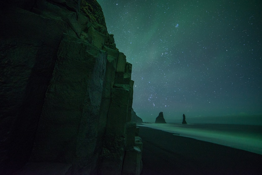 Aurora appear on the black sand beach. Photo by Chris Ried on Unsplash