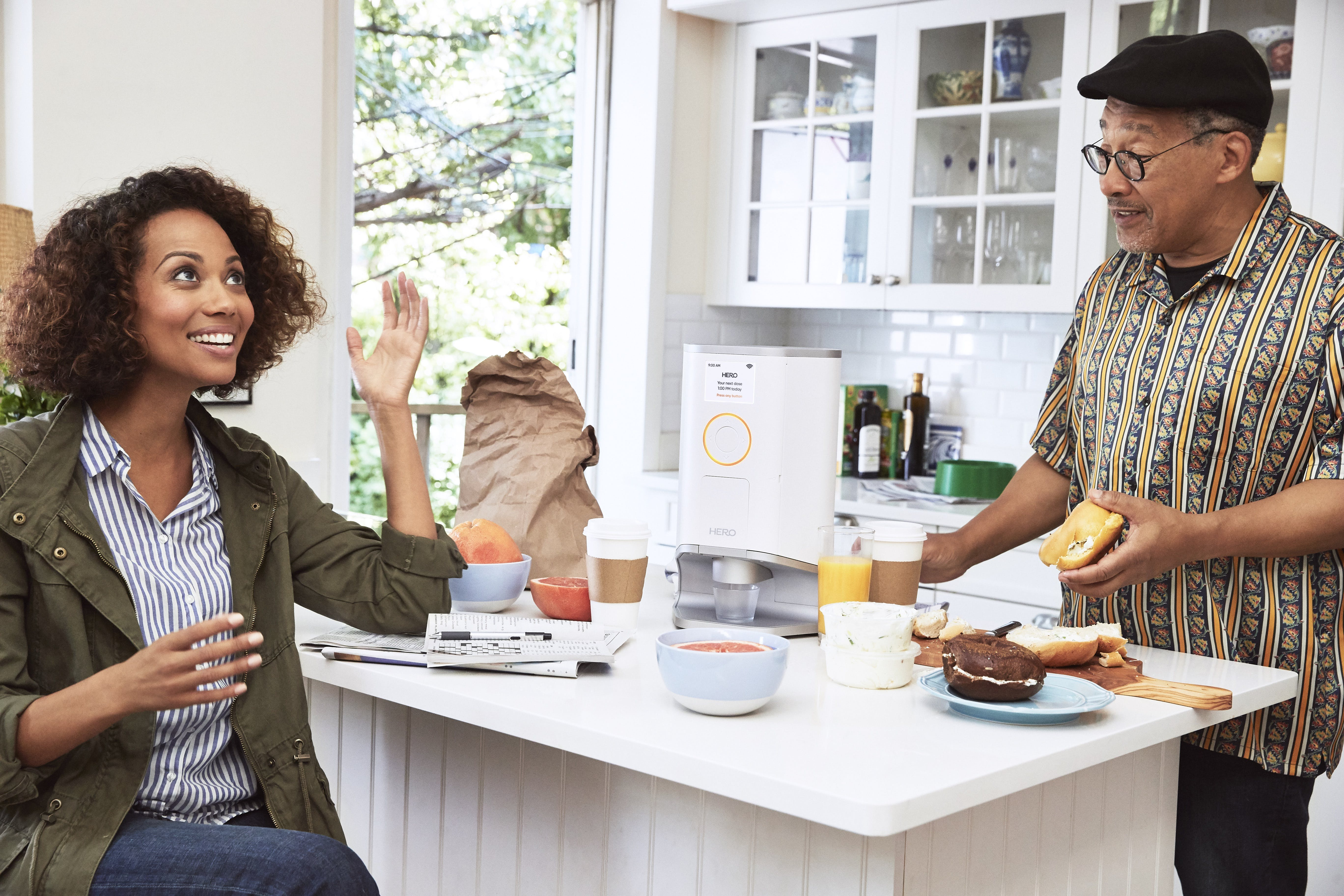 A father and daughter conversing and preparing breakfast around a kitchen island, with the Hero smart device in between them on the counter.