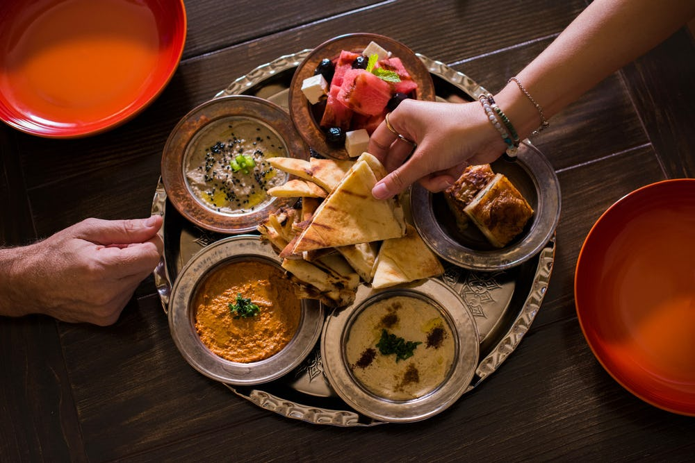 Image of two hands reaching for Turkish food appetizers on a table