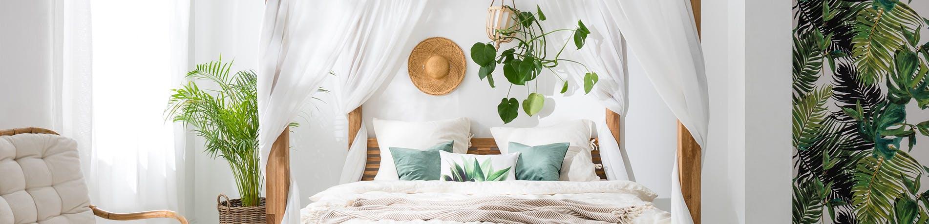 Schlafzimmer mit Pflanzentapete und Gründpflanzen als Deko für frisches Raumklima