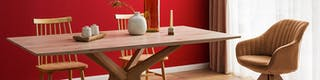Esstisch mit zwei Holzstühlen und gepolstertem Sessel vor rot gestrichener Wand