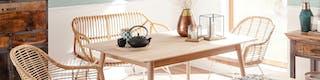 Rechteckiger, heller Tisch aus Holz umringt von leichten Korbstühlen mit Vase, Geschirr und Kerzen