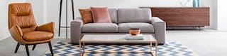 Wohnzimmer zoniert durch graues Sofa und Teppich in Rautenmuster daneben cognacfarbener Sessel und Sideboard aus Holz