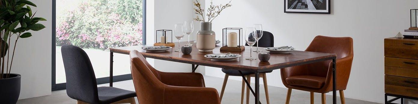 Gedeckter Tisch mit dünner Massivholzplatte und daran stehenden verschiedenen Esszimmerstühlen mit Ausblick nach draußen