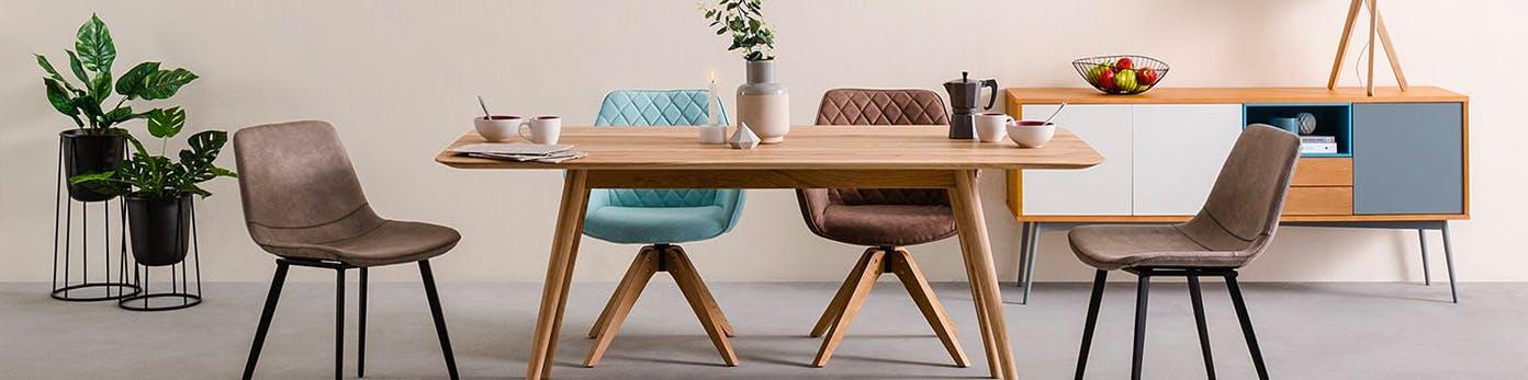 Rechteckiger Holztisch mit vier Stühle daran platziert sowie Grünpflanzen und Sideboard mit Obstschale