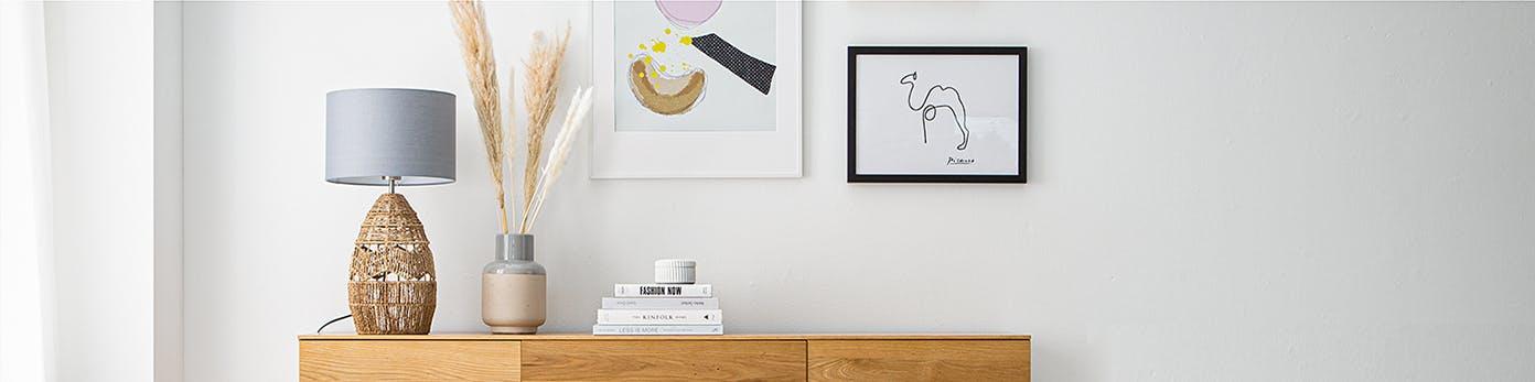 Lampe als gemütliche Lichtquelle auf Sideboard mit Vase und Büchern an Wand stehend mit aufgehangenen Bildern