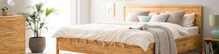 Schlafzimmer mit Bettgestell aus hellem Holz und frischer Bettwäsche in Pastellfarben abgerundet durch Zimmerpflanzen und aufgeräumte Kommode
