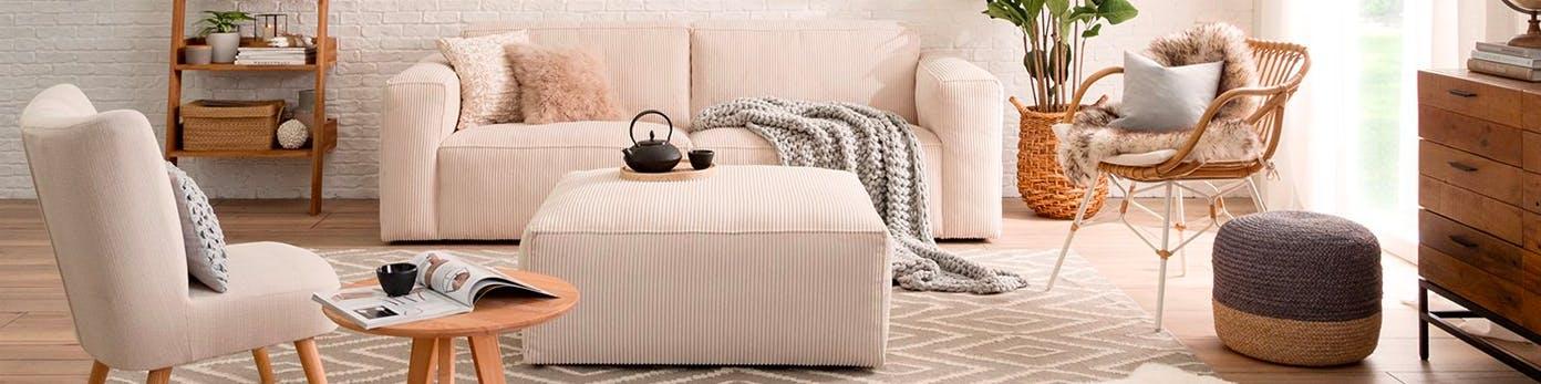 Zoniertes Wohnzimmer mit cremefarbenen Wohnmöbeln, Teppich in Rautenmuster, Korbstuhl mit Fell und Pouf